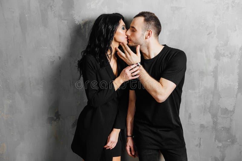Jong modieus mooi schitterend paar, tegen de grijze muurzolder in de studio of thuis stock fotografie