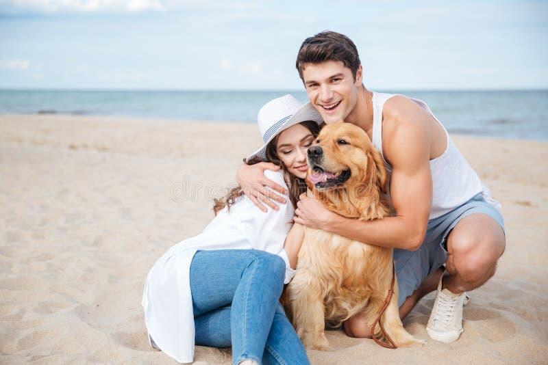 Jong modieus paar in liefdezitting het spelen met hond royalty-vrije stock afbeeldingen