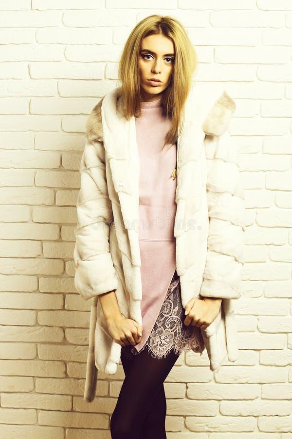 Jong modieus sexy mooi vrouw of meisje met mooi lang blondehaar in taillelaag van wit bont met roze kleding stock foto's