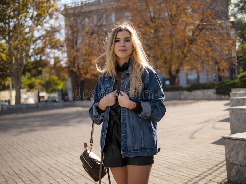 Jong modieus tienermeisje met stromend haar in een denimjasje in openlucht royalty-vrije stock afbeeldingen