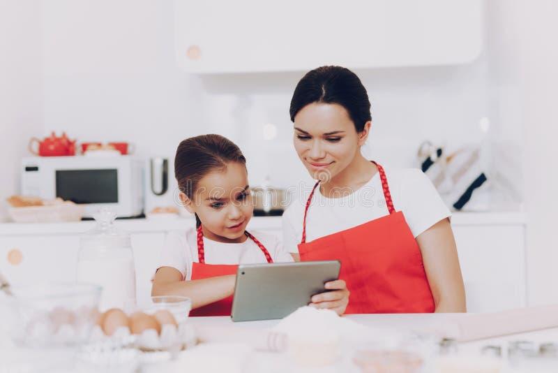 Jong Moeder en Meisje in Keuken Cook Sweet Cake stock foto's