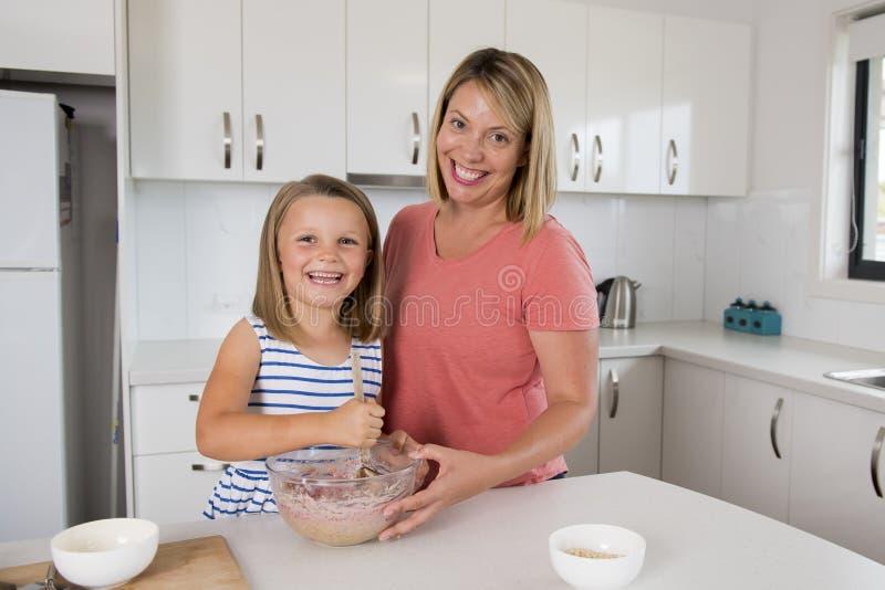 Jong moeder en snoepje weinig gelukkige thuis keuken van het dochterbaksel samen in het concept van de familielevensstijl stock afbeeldingen