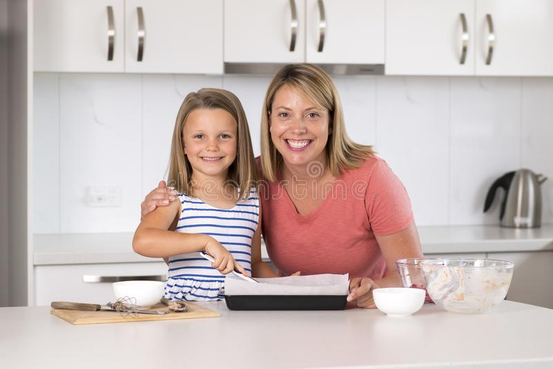 Jong moeder en snoepje weinig gelukkige thuis keuken van het dochterbaksel samen in het concept van de familielevensstijl royalty-vrije stock foto's