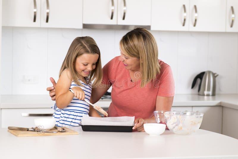 Jong moeder en snoepje weinig gelukkige thuis keuken van het dochterbaksel samen in het concept van de familielevensstijl royalty-vrije stock fotografie