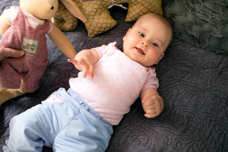 Jong mooi, aanbiddelijk meisje die op een bed met witte achtergrond liggen De ouder en het kind lachen samen en spelen Leuke baby stock foto