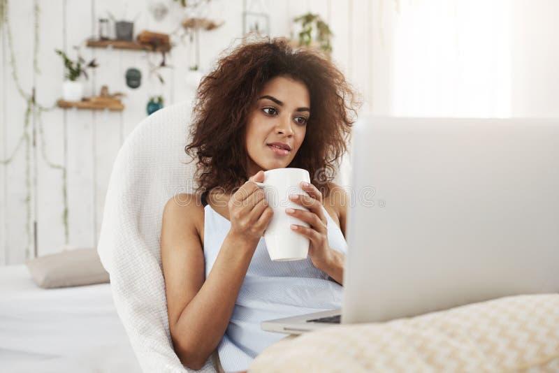 Jong mooi Afrikaans meisje die in nachtkleding laptop de zitting van de holdingskop als voorzitter thuis bekijken royalty-vrije stock foto's
