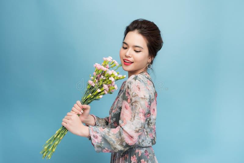 Jong mooi Aisa meisje die een boeket op blauwe achtergrond houden royalty-vrije stock foto