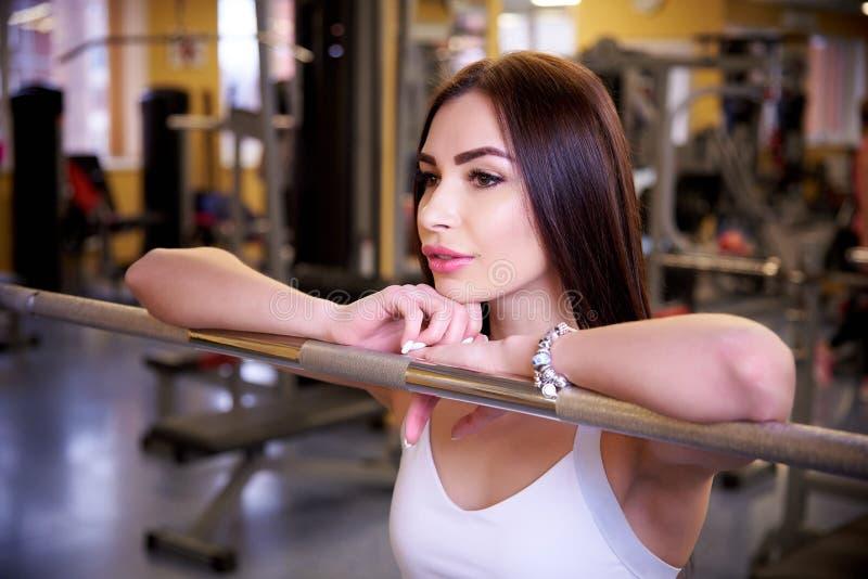 Jong mooi atletisch meisje dichtbij barbell in de gymnastiek royalty-vrije stock fotografie