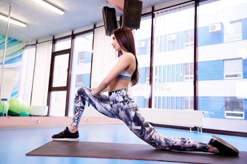 Jong mooi atletisch meisje die sport in de gymnastiek uitoefenen royalty-vrije stock foto's