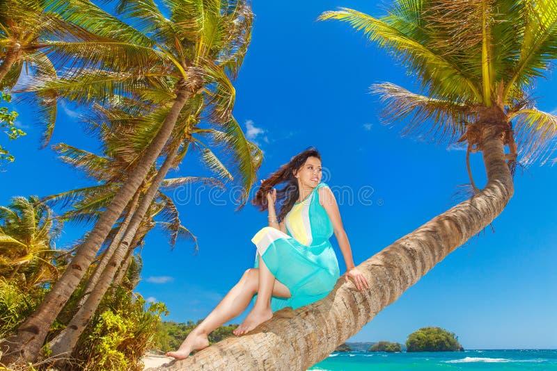 Jong mooi Aziatisch meisje op de palm op een tropisch strand royalty-vrije stock fotografie