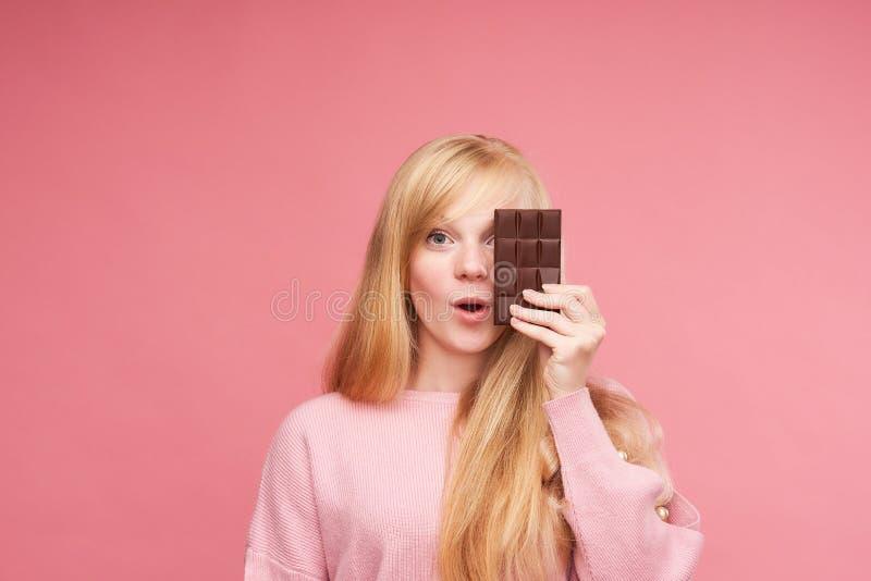 Jong mooi blonde met chocolade de betenchocolade van het tienermeisje de verleiding om verboden chocolade te eten vrolijk positie royalty-vrije stock foto's