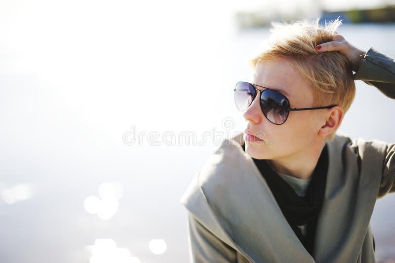 Jong mooi blondemeisje die dichtbij het water zonnebaden Het dragen van Zonnebril buiten stock foto