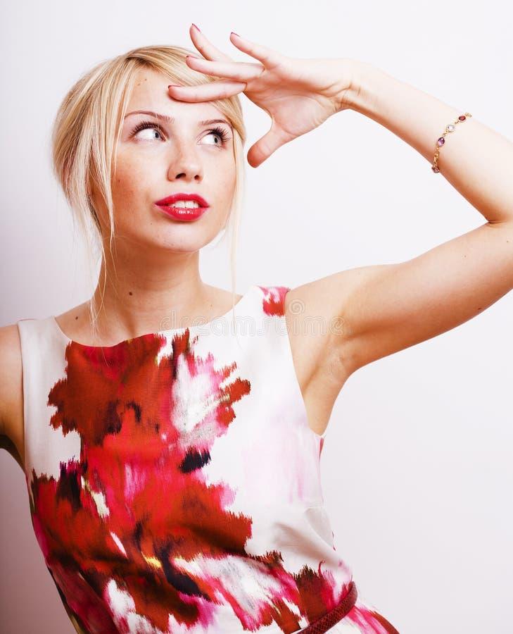 Jong mooi blondemeisje die iets voorstellen bij het witte exemplaar ruimte, emotionele stellen, het concept van levensstijlmensen stock foto's