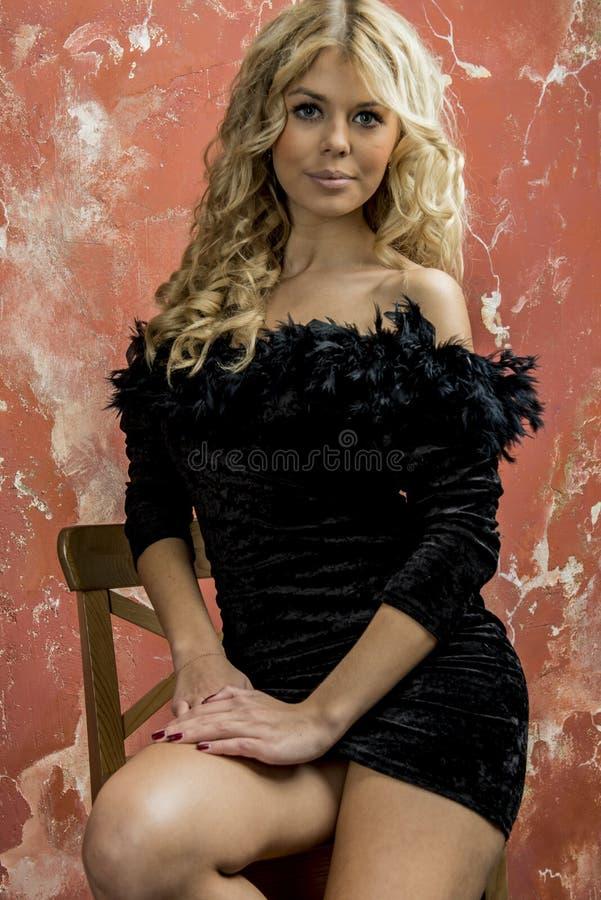 Jong mooi blondemeisje in een zwarte cocktailkleding stock fotografie