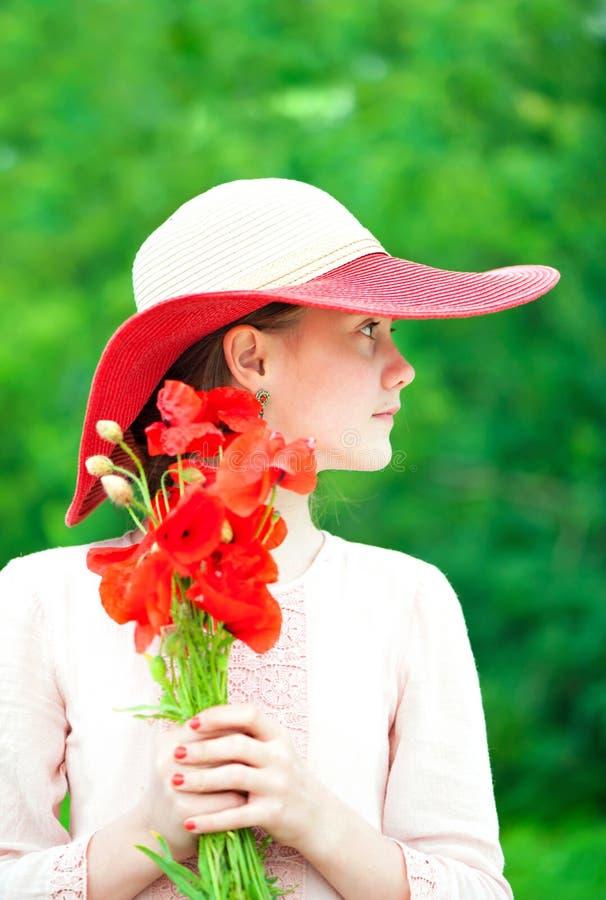 Jong mooi dame/meisje in rode hoed met het boeket van papaverbloemen royalty-vrije stock fotografie