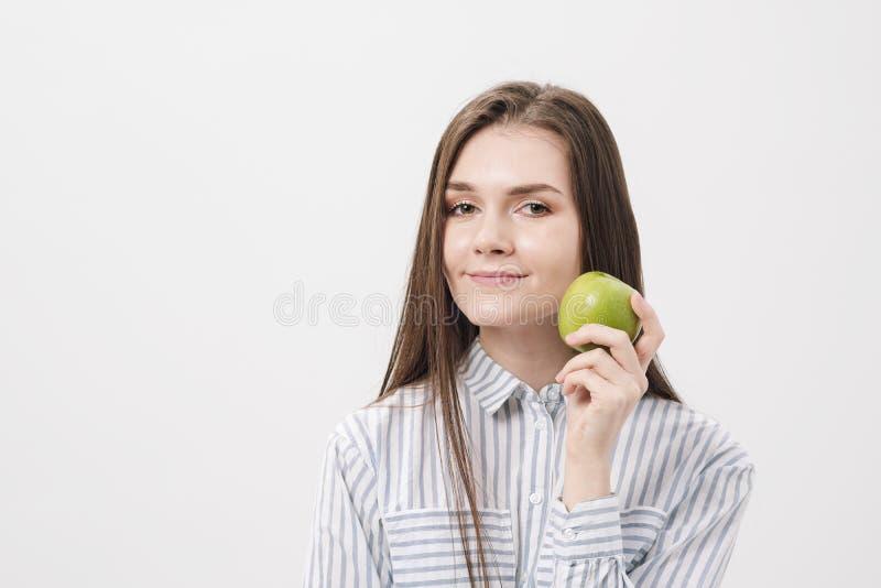 Jong mooi donkerbruin meisje op een witte achtergrond die een verse groene appel houden stock afbeelding