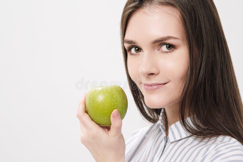 Jong mooi donkerbruin meisje op een witte achtergrond die een verse groene appel houden royalty-vrije stock foto's