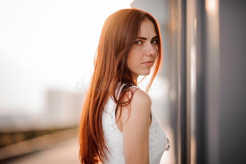 Jong mooi donkerbruin portret op de straat Meisje in kleding in openlucht De heldere stralen van de zon Zonsondergang stock afbeelding