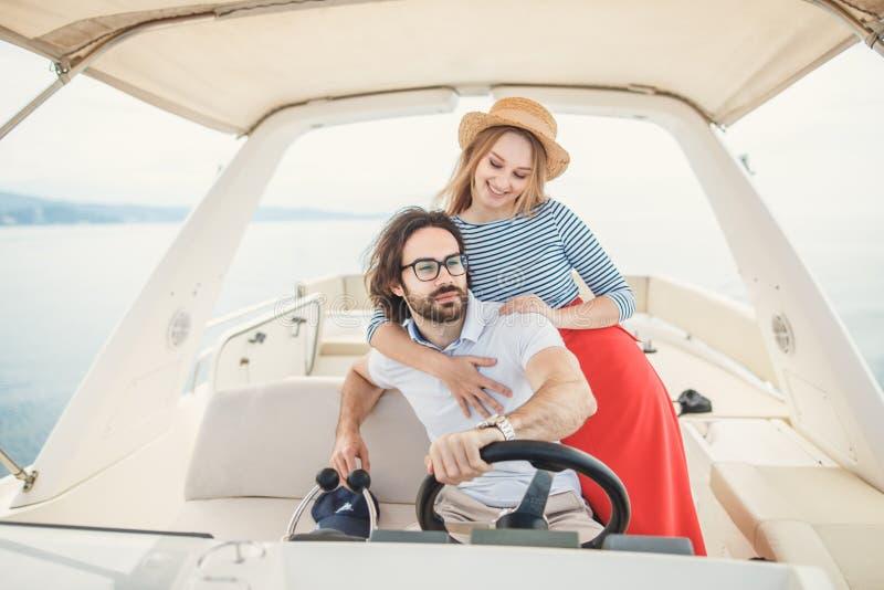 Jong mooi echtpaar die op het jacht op vakantie omhelzen stock afbeeldingen