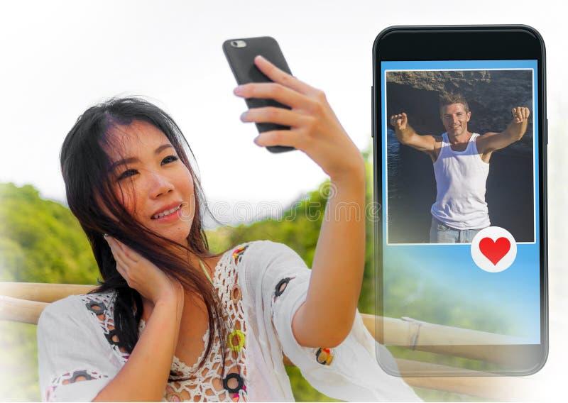 Jong mooi en gelukkig Aziatisch Chinees meisje die het online dateren app van Internet op mobiele telefoon gebruiken die als beri stock afbeeldingen