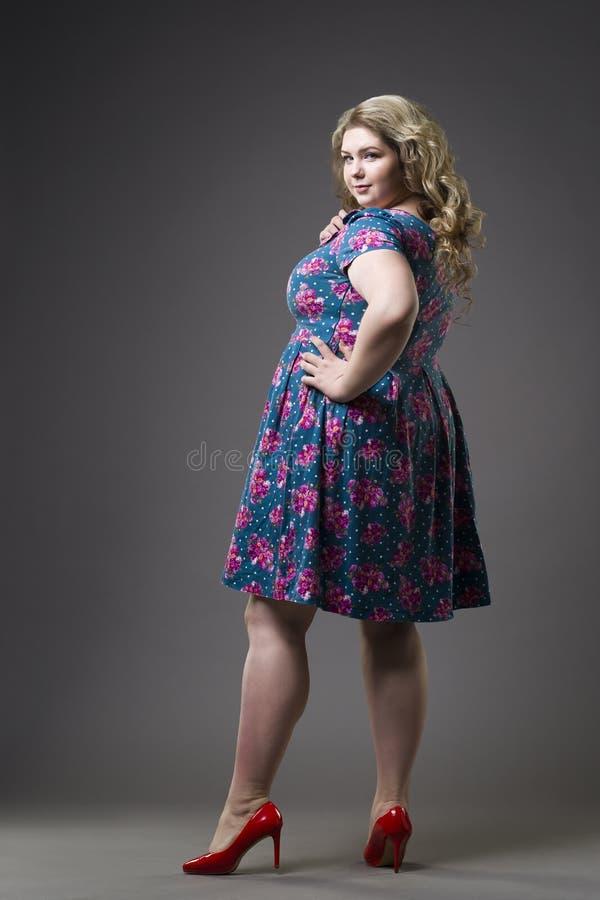 Jong mooi gelukkig blonde plus groottemodel in kleding en schoenen, xxl vrouw op grijze studioachtergrond royalty-vrije stock fotografie