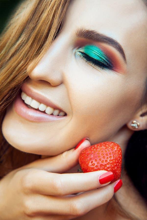 Jong mooi gelukkig grappig meisje met rode kleding en make-upholdingsaardbei in zomer in het park royalty-vrije stock foto's