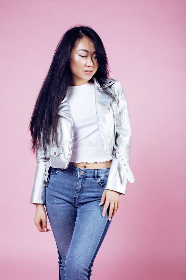 Jong mooi glimlachend Aziatisch Koreaans meisje die moderne manierclothers op roze achtergrond, het concept van levensstijlmensen stock foto