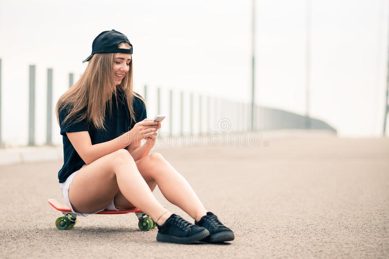 Jong Mooi Glimlachend Blondemeisje die Smartphone gebruiken terwijl het Zitten op het Skateboard royalty-vrije stock afbeelding