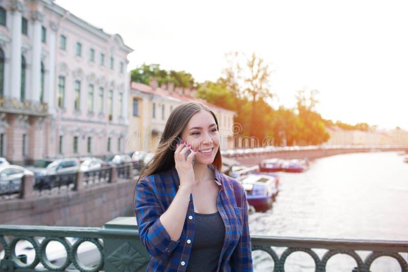 Jong mooi glimlachend hipster meisje die op mobiele telefoon spreken, die zich in openlucht dichtbij dijkrivier bevinden stock afbeelding