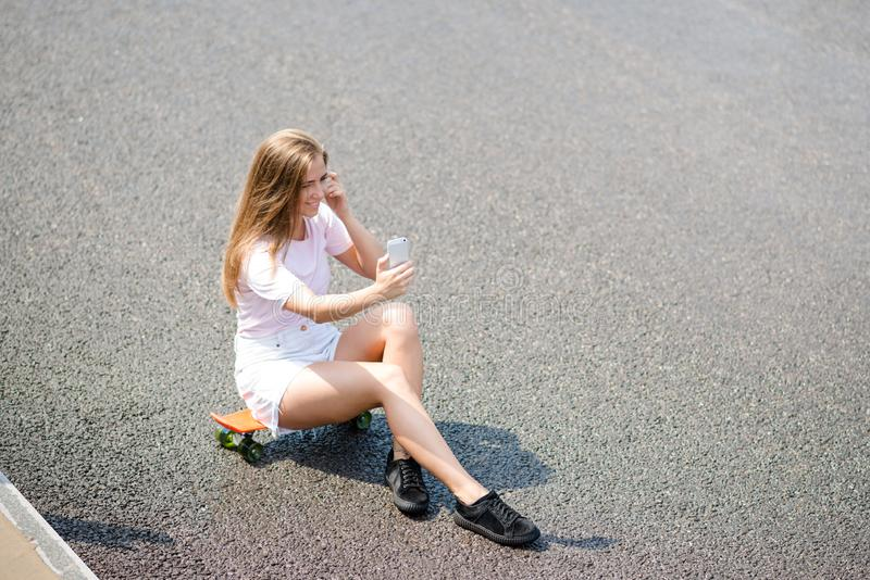 Jong Mooi Glimlachend Meisje die Selfie met Smartphone maken terwijl het Zitten op het Skateboard op de Weg royalty-vrije stock afbeeldingen