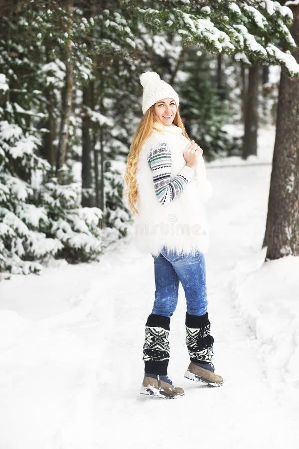 Jong mooi glimlachend meisje in openlucht bij de winterbos stock foto's