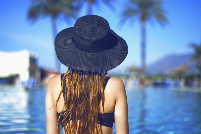 Jong mooi glimlachmeisje in zwarte manierhoed, rode lippen en lang haar, die dichtbij pool beackground van palmen stellen royalty-vrije stock foto's