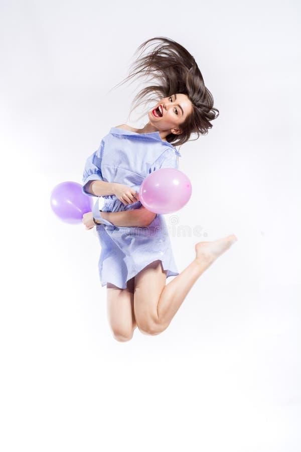 Jong mooi het glimlachen vrouwen gestreept blauw en wit overhemd die met ballons tegen witte achtergrond springen stock fotografie
