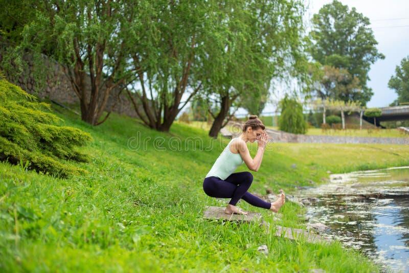 Jong mooi Kaukasisch donkerbruin meisje die yoga op een groen gazon doen tegen de achtergrond van de rivier royalty-vrije stock afbeeldingen