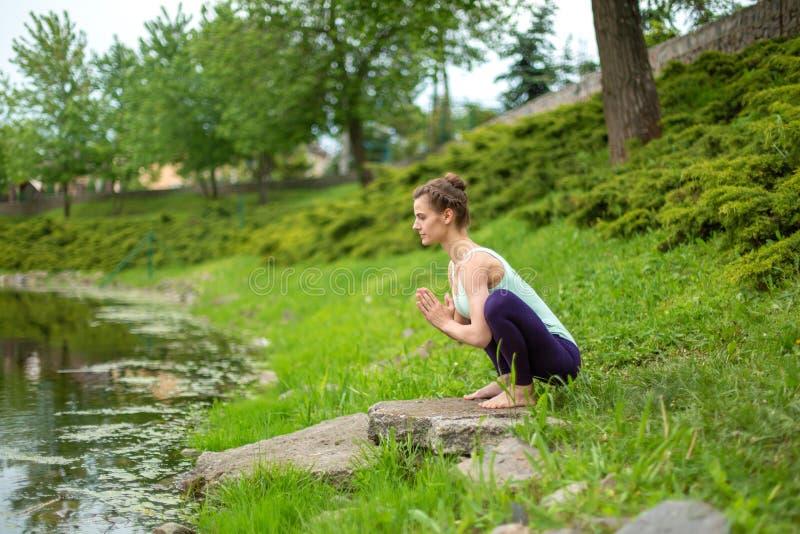 Jong mooi Kaukasisch donkerbruin meisje die yoga op een groen gazon doen tegen de achtergrond van de rivier royalty-vrije stock foto's