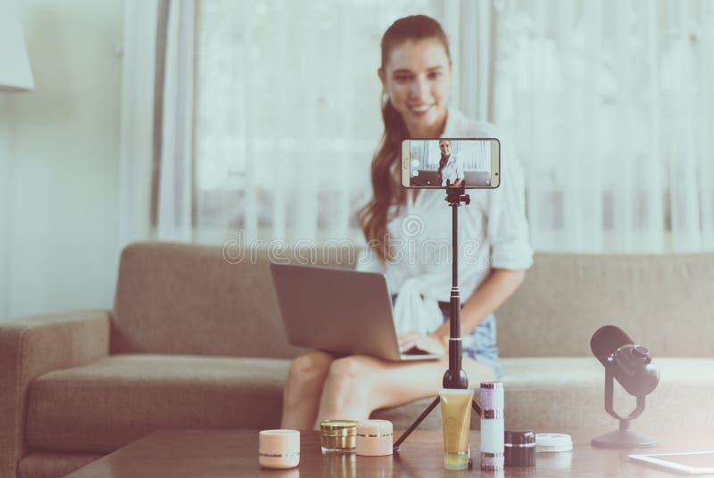 Jong mooi Kaukasisch van de vrouwen blogger levend overzicht en demonstratie schoonheidsmiddelenproduct op het mobiele scherm van stock foto's