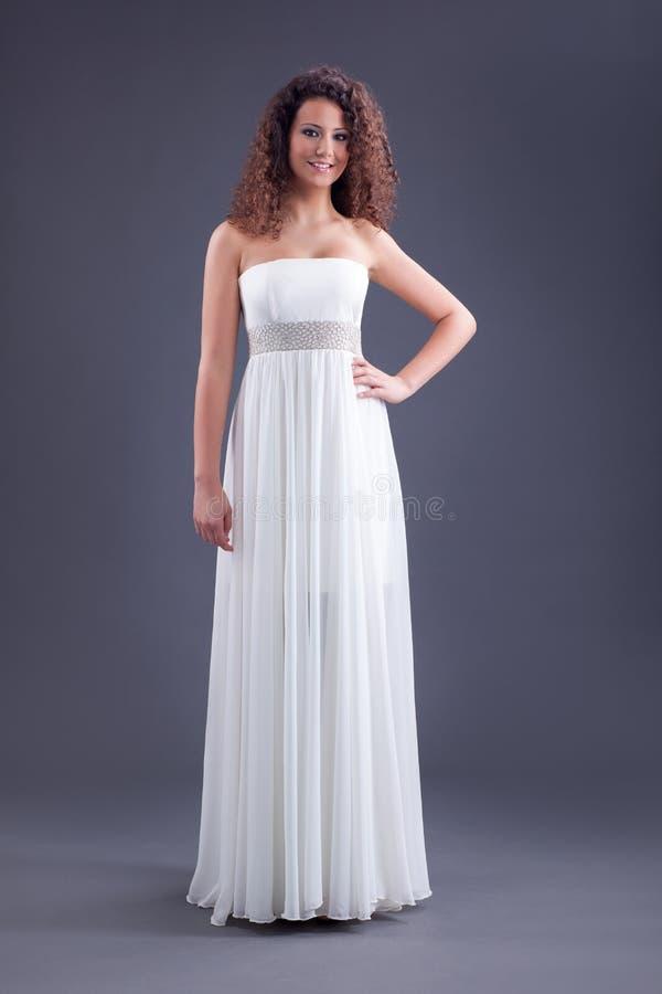 Jong mooi krullend vrouwelijk model in witte kleding stock afbeeldingen