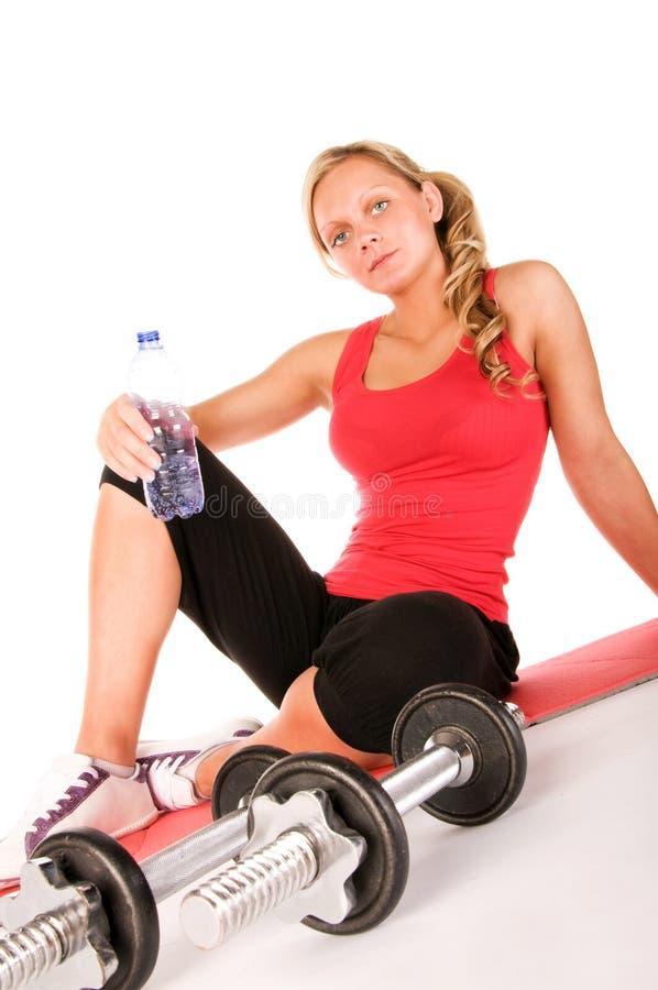 Jong mooi meisje bij het gymnastiek drinkwater royalty-vrije stock fotografie