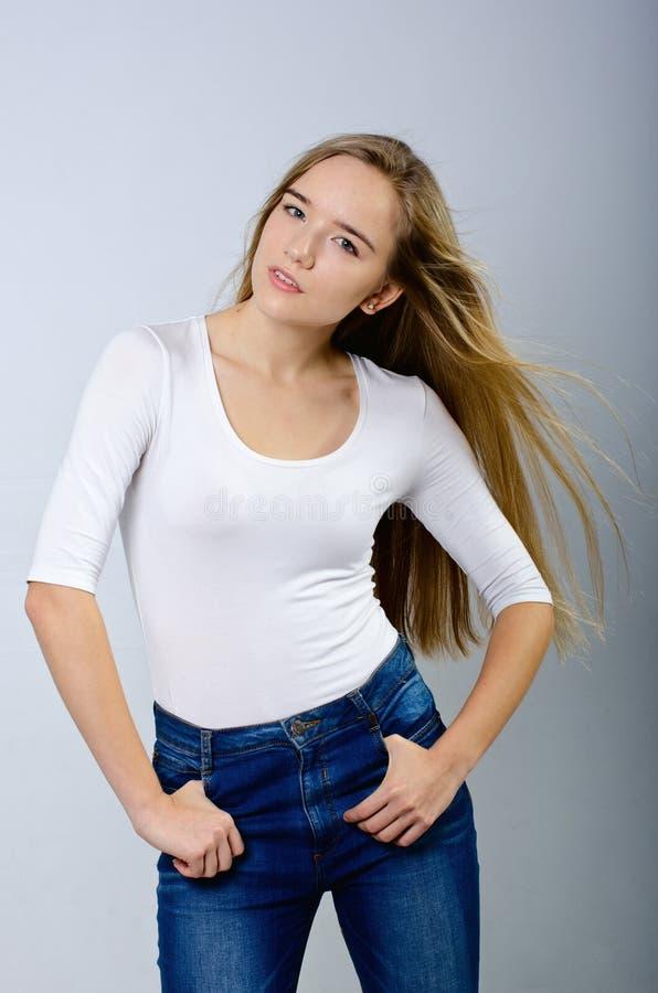 Jong mooi meisje in col en jeans stock foto