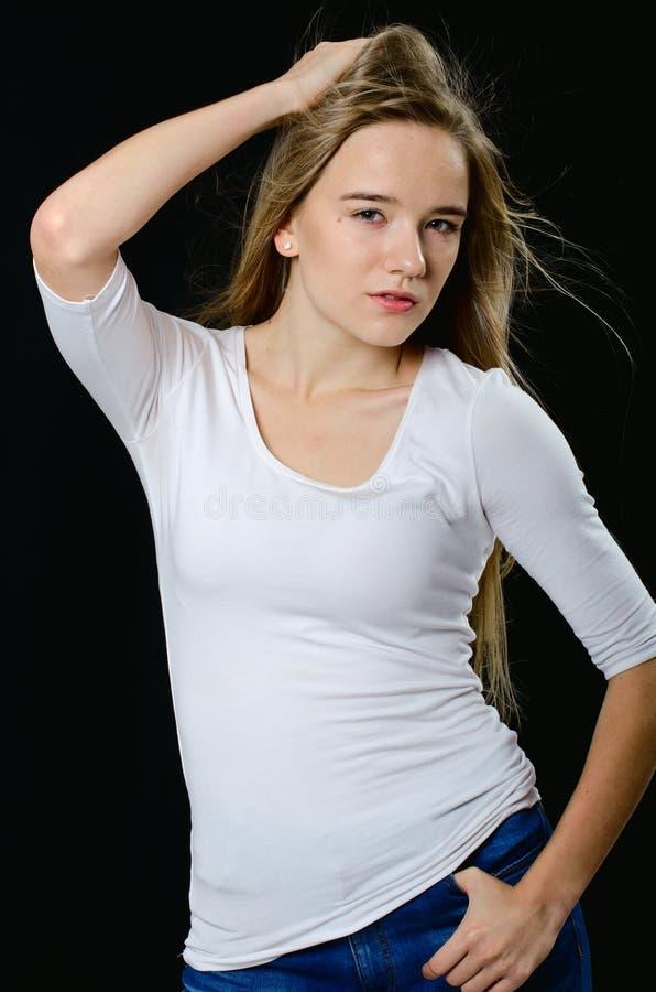 Jong mooi meisje in col en jeans stock afbeeldingen
