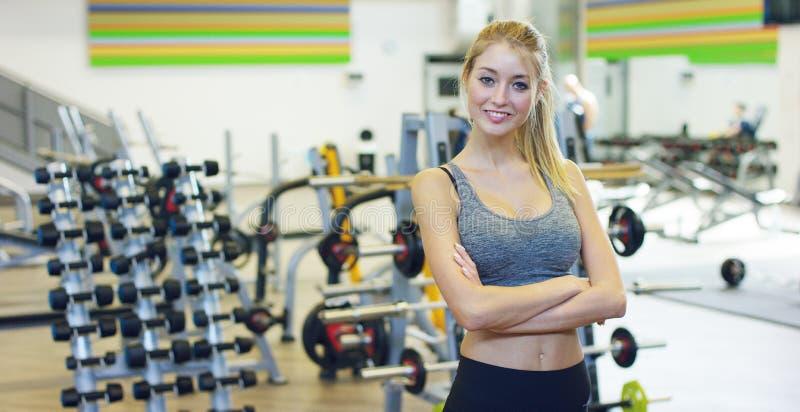 Jong mooi meisje in de gymnastiek, tribunes die met een handdoek op haar schouder na het trainen glimlachen en ontspannen Concept stock foto