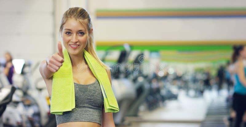 Jong mooi meisje in de gymnastiek, tribunes die met een handdoek op haar schouder na het trainen glimlachen en ontspannen Concept stock afbeeldingen
