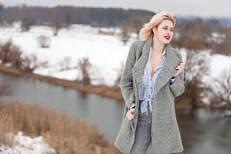 Jong mooi meisje in de lente tegen achtergrond van rivier royalty-vrije stock afbeelding