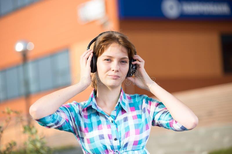 Jong mooi meisje die aan muziekspeler luisteren op de straat stock afbeeldingen