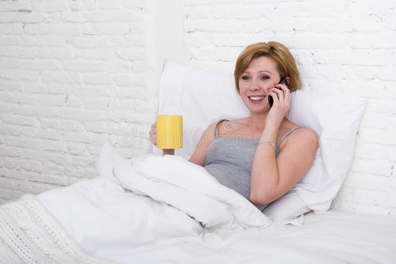 Jong mooi meisje die coffe op bed hebben terwijl het letten van Internet-op nieuws in zijn mobiele telefoon in online mededeling royalty-vrije stock foto's