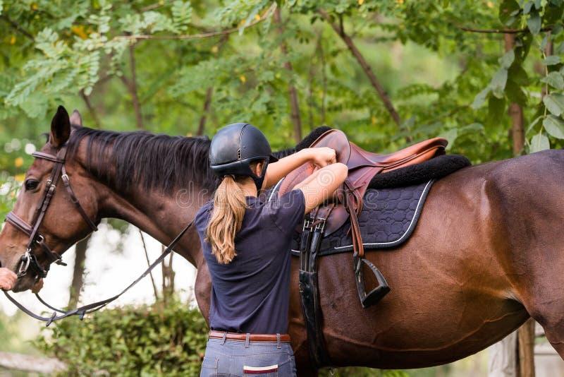 Jong mooi meisje die een paard met backlit erachter bladeren berijden stock foto