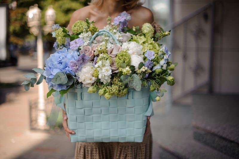 Jong mooi meisje die een reusachtige mand van tedere bloemen houden stock foto's