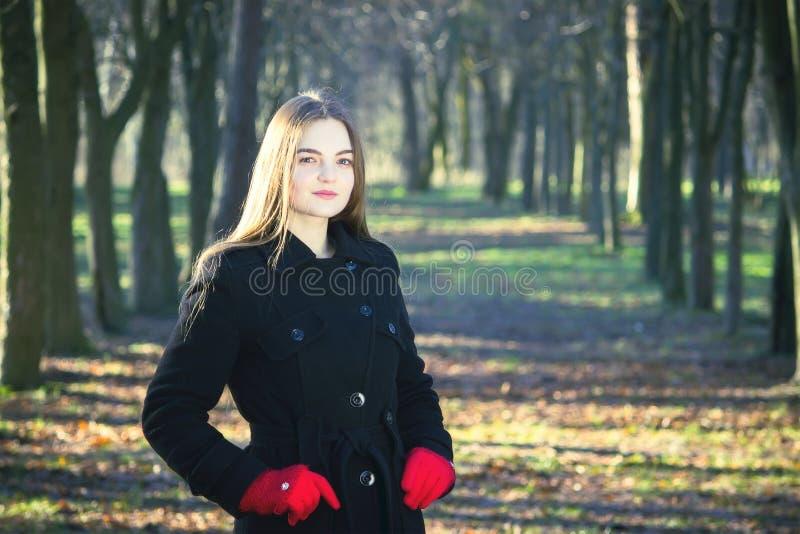 Jong mooi meisje die in een zwarte laag rode handschoenen park van de de lente het bosrook onderzoeken stock fotografie