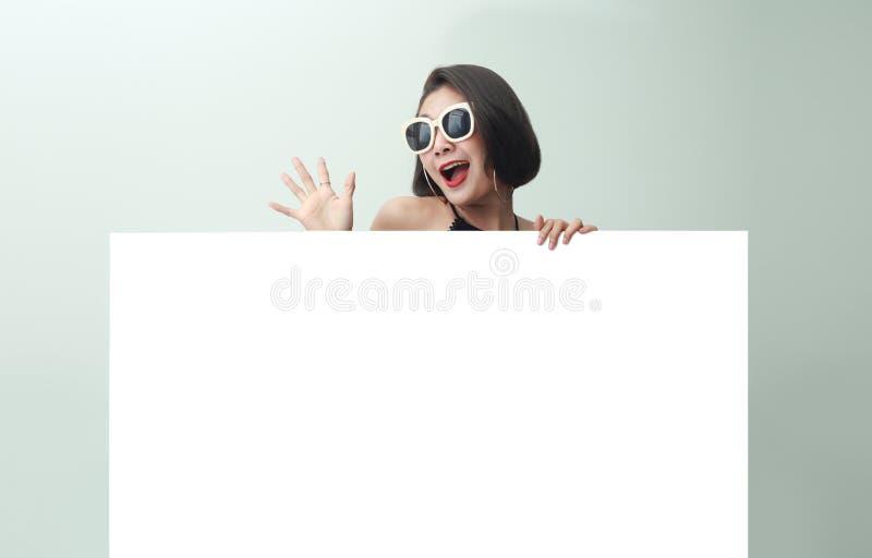 Jong mooi meisje die en een leeg blad van document glimlachen houden royalty-vrije stock afbeelding