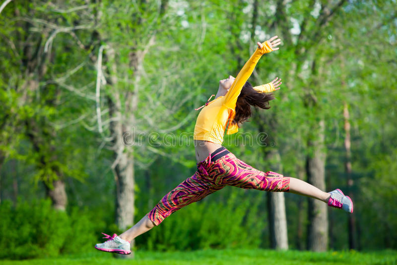Jong mooi meisje die gymnastiek- sprongen doen royalty-vrije stock afbeelding